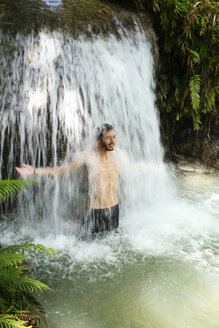 Philippines, Siquijor, man enjoying flowing water of Cambugahay waterfall - GEMF000130