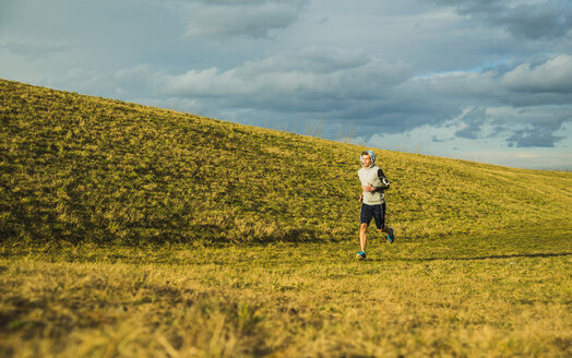 Germany, Mannheim, young man jogging in meadow - UUF003629
