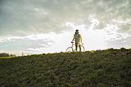 Germany, Mannheim, young man standing with bicycle - UUF003635