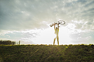 Germany, Mannheim, young man cheering with bicycle - UUF003636