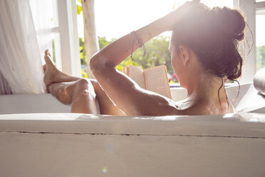Woman relaxing in bathtub reading book - MBEF001334