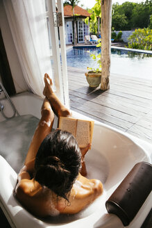 Woman relaxing in bathtub reading book - MBE001350