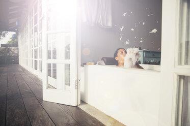 Woman in bathtub blowing foam - MBEF001341