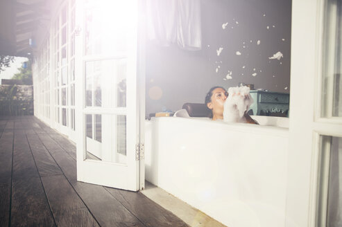 Woman in bathtub blowing foam - MBEF001341