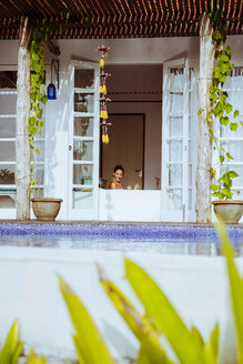 Indonesia, Bali, happy woman in bathtub - MBEF001342