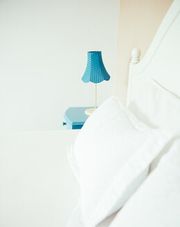 Indonesia, Bali, table lamp on blue bedside cabinet and bed in bedroom of a holiday villa - MBEF001347