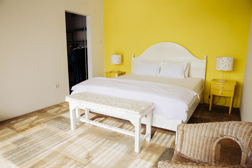 Indonesia, Bali, bedroom with yellow wall and yellow bedside cabinets of a holiday villa - MBEF001353