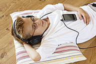 Boy with MP3 Player and headphones listening music - LBF001093