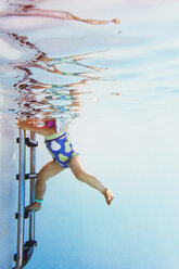 Underwater shot of toddler girl standing on boarding ladder in swimming pool - LS000060