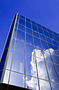 Germany, Bielefeld, glass facade of a commercial house with reflection of cloud - HOHF001306