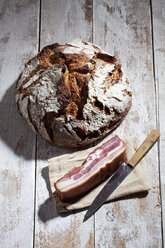 Loaf of brown bread, bacon on cloth and a knife - CSF025026