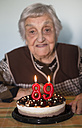 Old woman celebrating her 89th birthday - RAEF000097