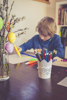 Boy painting with Easter decoration in foreground - SARF001541