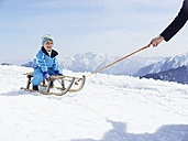 Germany, Tegernsee, Wallberg, smiling little boy sitting on sledge - EDF000135