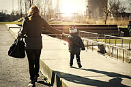 Germany, Oberhausen, toddler walking with mother in park - GDF000696