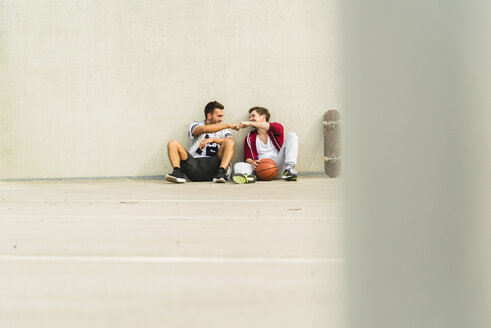 Two young men sitting with skateboard and basketball on parking level - UUF003685