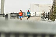 Two young men jogging on bridge - UUF003703