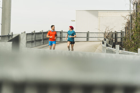 Two young men jogging on bridge - UUF003703