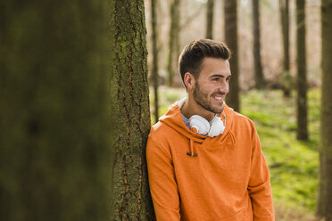 Smiling young man with headphones in forest - UUF003721
