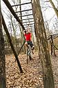 Two young men brachiating on climbing frame - UUF003728