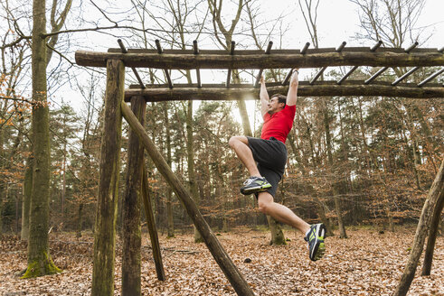 Young man brachiating on climbing frame - UUF003731