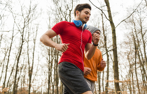 Two young men jogging in forest - UUF003733