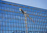 Germany, Hamburg, glass facade with reflection of construction crane - KRPF001391