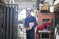 Smiling warehouseman with clipboard in storehouse - SGF001409