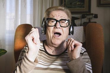 Portrait of happy elderly lady hearing music with headphones - GEMF000138