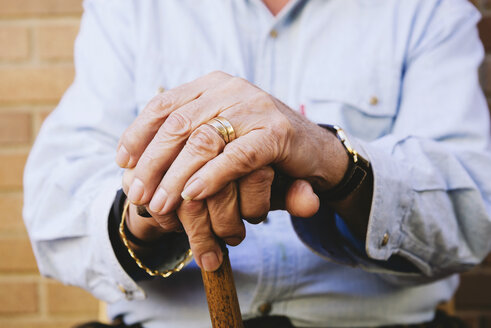 Close-up of old man's hands resting on a cane - GEMF000141