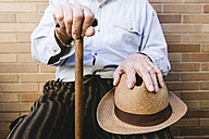 Close-up of old man with cane and straw hat - GEMF000144