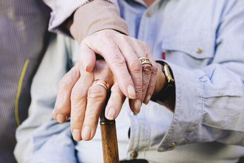 Close-up of old man's and woman's hands resting on a cane - GEMF000147