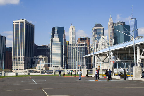 USA, New York, Brooklyn Bridge Park basketball courts on Pier 2 with Lower Manhattan skyscraper skyline beyond. - PSF000667