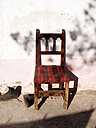 Spain, Catalonia, chair in pair of boots at sunlight - JMF000328