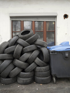 Germany, pile of old car tires and roll-out container in front of a house - JMF000333