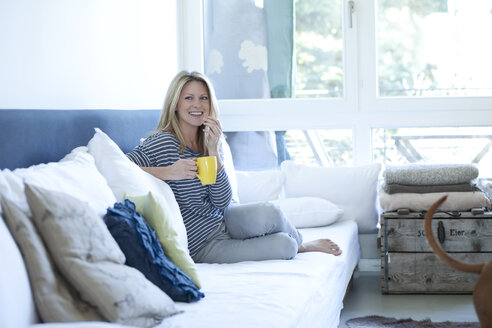 Relaxed woman sitting on couch with cup of coffee - MAEF009964