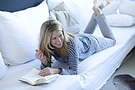 Smiling woman lying on couch with a book - MAEF009978