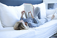 Woman lying on couch reading a book - MAEF009981