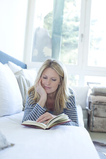 Woman lying on couch reading a book - MAEF009989