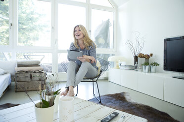 Smiling blond woman with digital tablet at home - MAEF010010