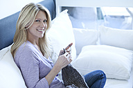 Portrait of smiling blond woman sitting on couch knitting - MAEF010030