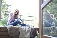 Blond woman sitting on balcony telephoning - MAEF010040
