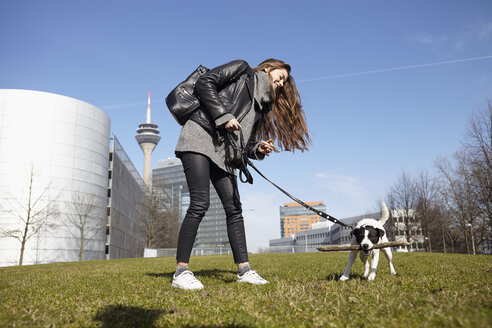 Germany, Dusseldorf, Young woman playing with her dog - RHF000656