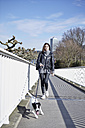 Germany, Dusseldorf, Young woman walking her dog - RHF000668