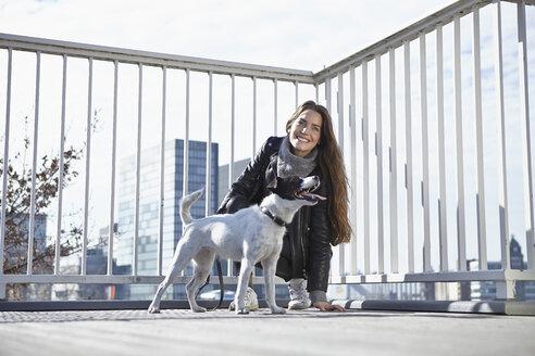 Germany, Dusseldorf, Young woman walking her dog - RHF000671