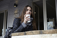 Germany, Dusseldorf, Young woman with coffee sitting outdoor - RHF000680