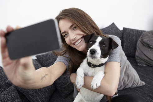 Young woman taking selfie with dog - RHF000747