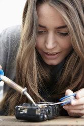 Young woman repairing camera - RHF000722