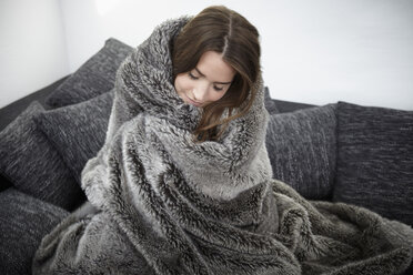 Young woman on couch wrapped in fur blanket - RHF000731