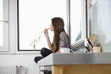 Young woman in kitchen sitting at window eating carrot - RHF000739